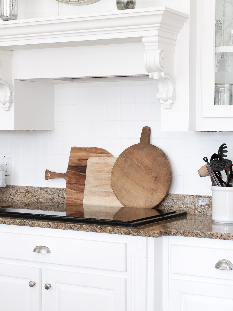 Create warmth in a white kitchen using cutting boards for White cutting board used for